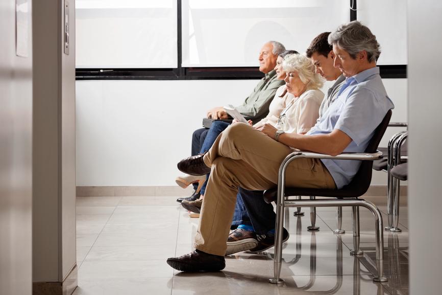 Fileira-de-pessoas-multiétnicas-sentados-lado-a-lado-enquanto-esperam-por-médico-no-saguão-do-consultório.