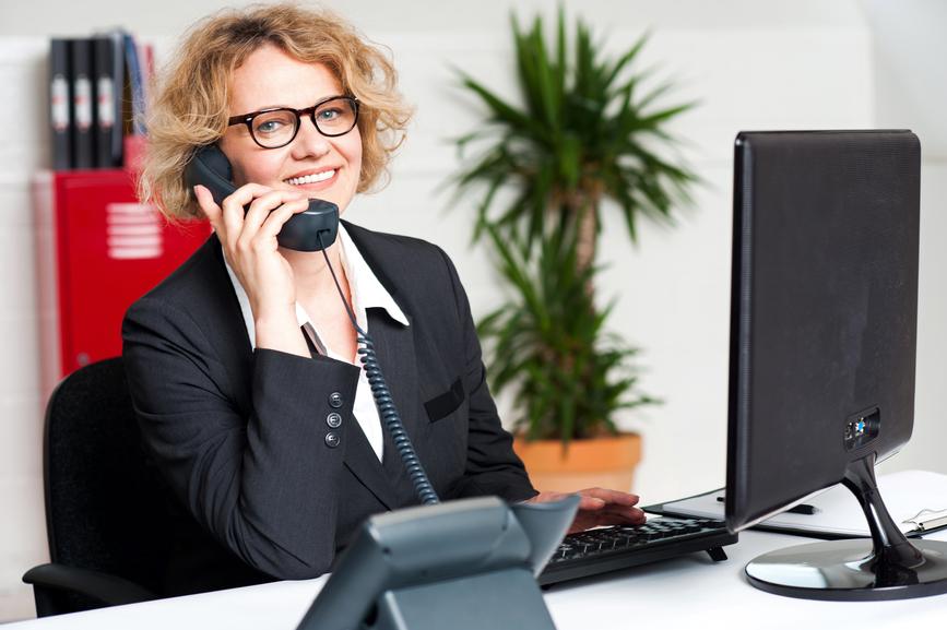 Foto-de-secretária-sorrindente-atendendo-telefonema-de-clientes-em-um-escritório