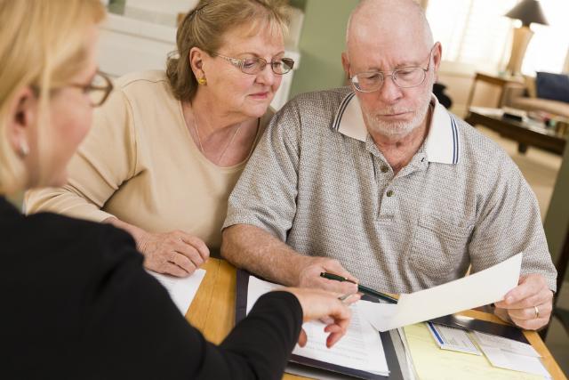 fotografia-casal-de-idosos-preocupados-com-gastos-analizando-documentos-com-secretária-desfocada-na-imagem-em-primeiro-plano.