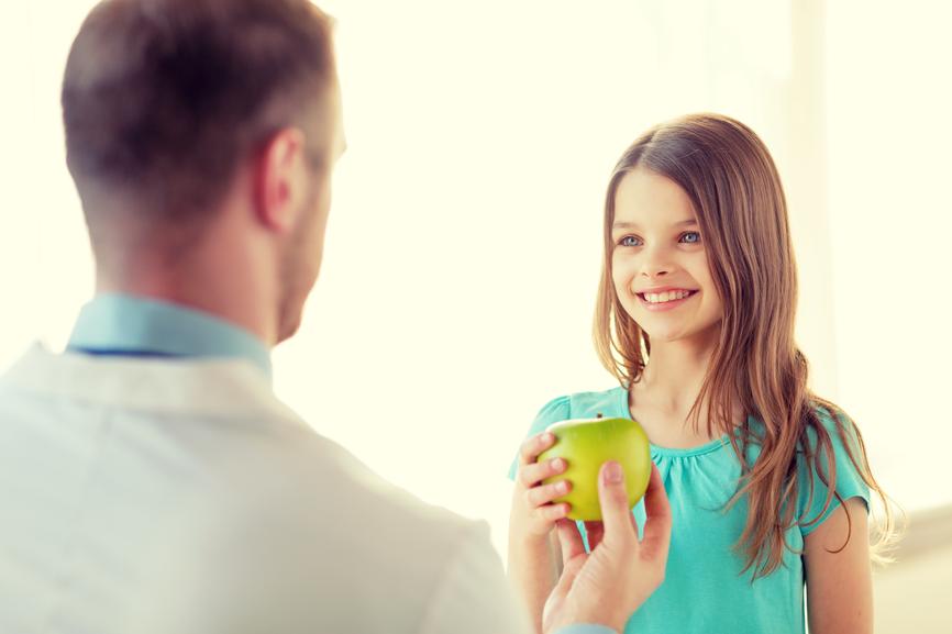 fotografia-menina-sorridente-recebendo-maçâ-verde-de-um-dentista